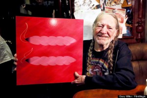 """AUSTIN, TX - MARCH 27:  Willie Nelson holds up the Human Rights Campaign marriage equality symbol that has been stylized into two """"joints"""" during an interview on his bus the Honeysuckle Rose on March 27, 2013 in Austin, Texas.  (Photo by Gary Miller/FilmMagic)"""